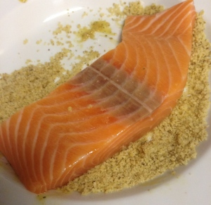 press salmon filet into crushed walnuts
